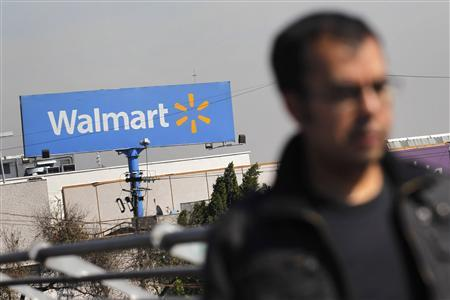 A person walks near a Wal-Mart billboard in Mexico City